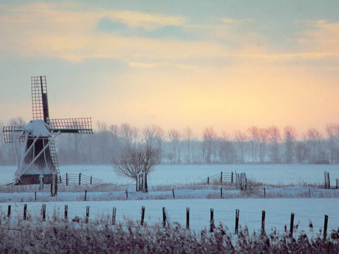 Zonsondergang in winterse landschap met sneeuw en windmolen